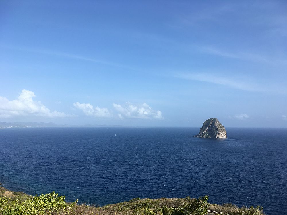 A view over  a calm blue ocean with one bare, pointed rock sticking up out of it.