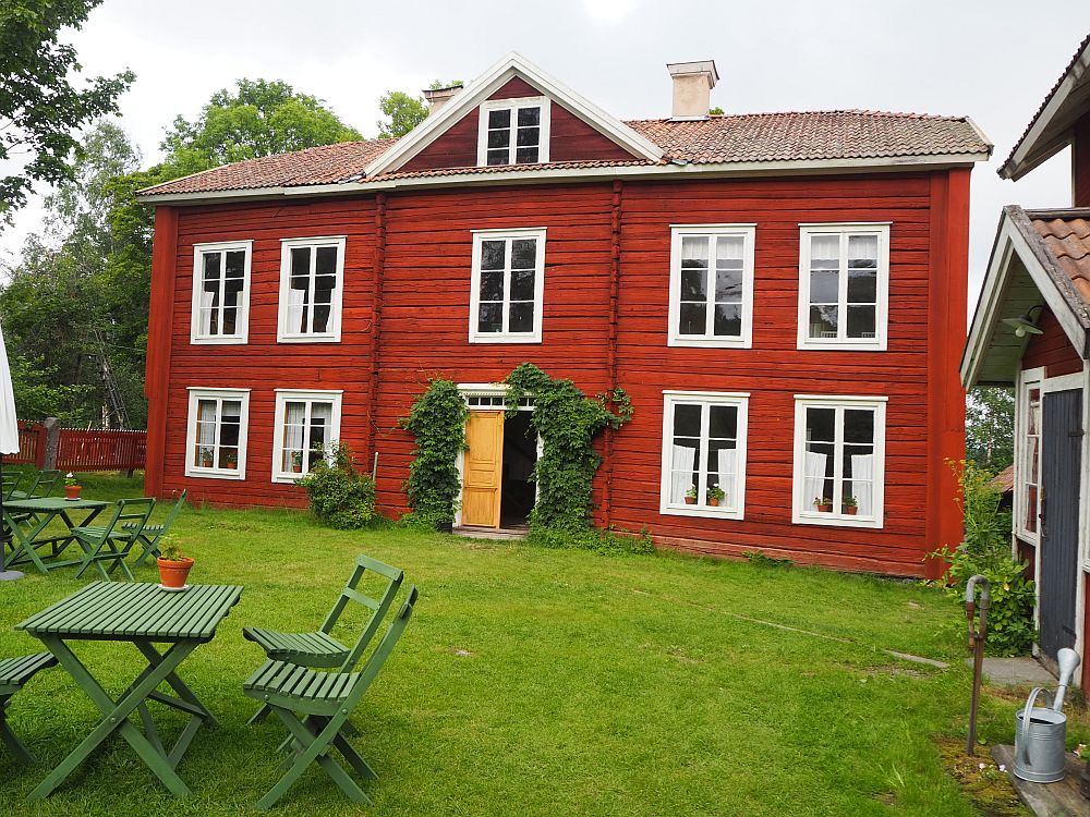 The house is red-painted wood. The door sits right in the middle with two windows on either side of it. Upstairs is one more story: one window in the center above the door and two windows on either side.