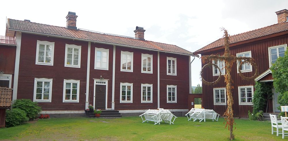 The house is dark red with white edging. The photo shows the center house and only part of the right-hand side house. The central house is not symmetrical: The door has 2 windows to the left of it and 3 to the right. The house has two stories.