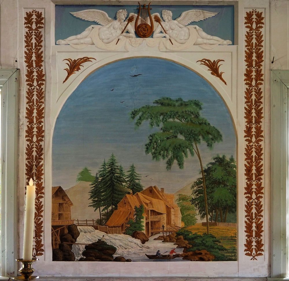 The mural shows a rural scene: a thatched house next to a waterfall with trees around it. Above are two reclining angels that look 3-dimensional.