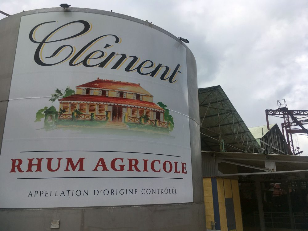 """A large round tank with a sign reading """"Clement Rhum Agricole Appellation d'origine Controlee."""""""