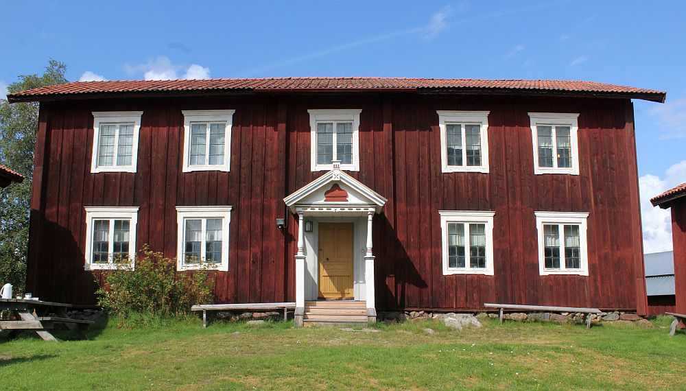 A simple red-painted house with white trim around the windows. The doorway is set right in the middle with a small roof over the entry. Two stories. Two windows on either side of the door and 5 windows upstairs.