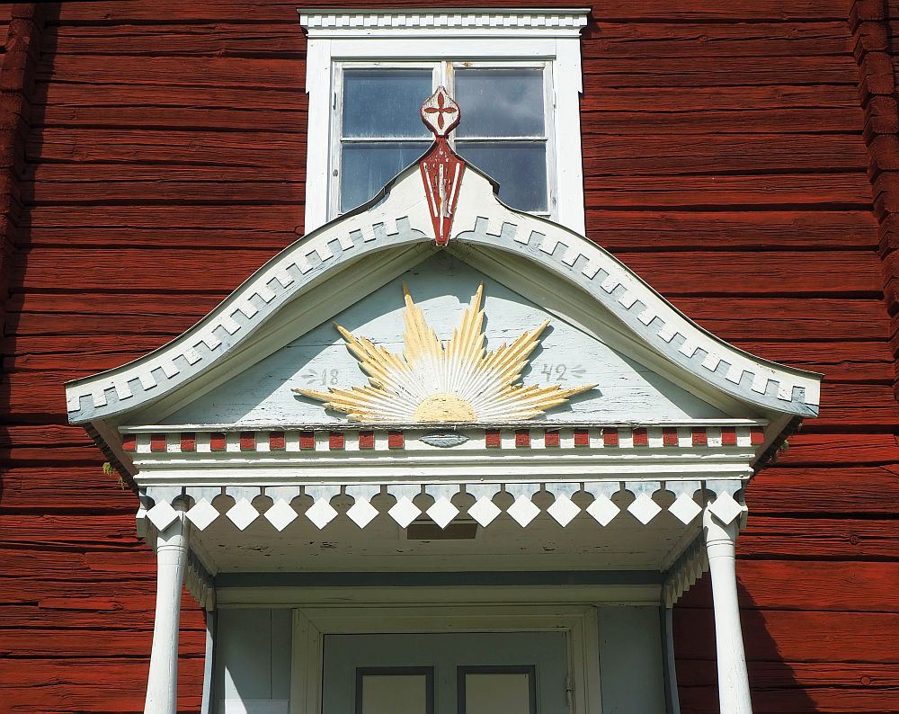 The roof over the front door is carved with a edge of pointy teeth. Above that is a half of a sun in the center of the little roof.