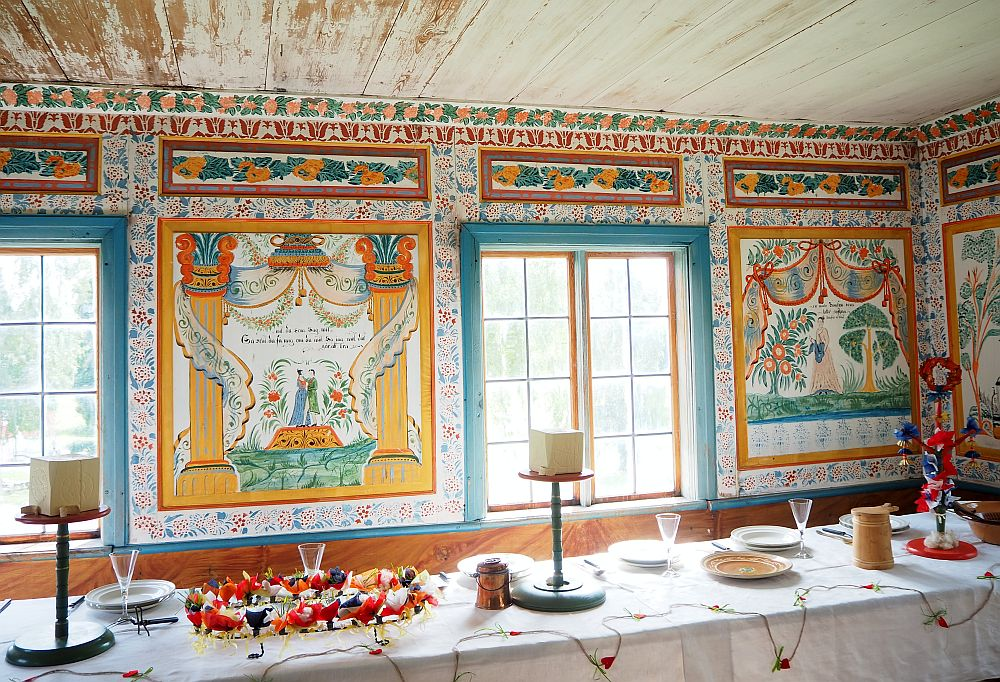 A long table at the bottom of the photo has a simple table setting with occasional colorful arrangements. Behind them are two windows with the walls between and above them completely filled with paintings: Large square murals between and next to the windows show scenes filled with flowers. The center one has a couple on a boat, I think, in the center and the other shows a woman standing among flowering trees. Around the murals and above them are ornate flowery patterns, and a different pattern follows the molding next to the ceiling. By contrast, the ceiling is plain white.