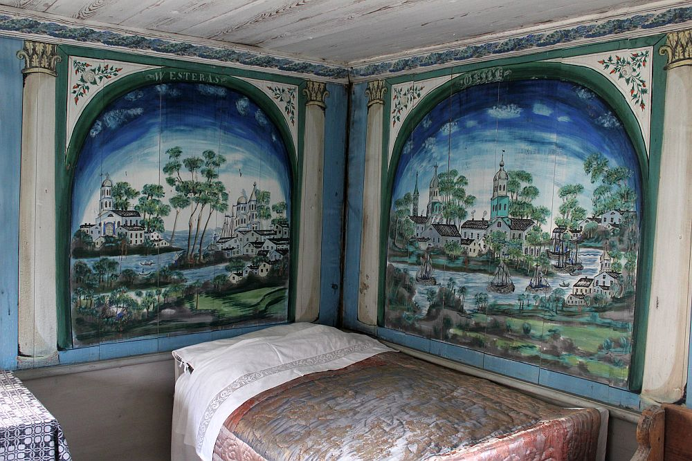 A bed in a corner. Above it, on each wall, a large painting filling each wall, arched at the top. Each painting shows a scene of white buildings, a church, a waterway with boats. The sky above is blue and the top edges are extra blue.