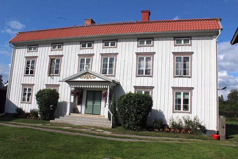 A large white house with three stories. The door sits symmetrically in the center with a large portico roof over the steps up. Two windows on either side of the central door. 6 windows on the story above that. 6 more windows (but much smaller) above that, under the roof.