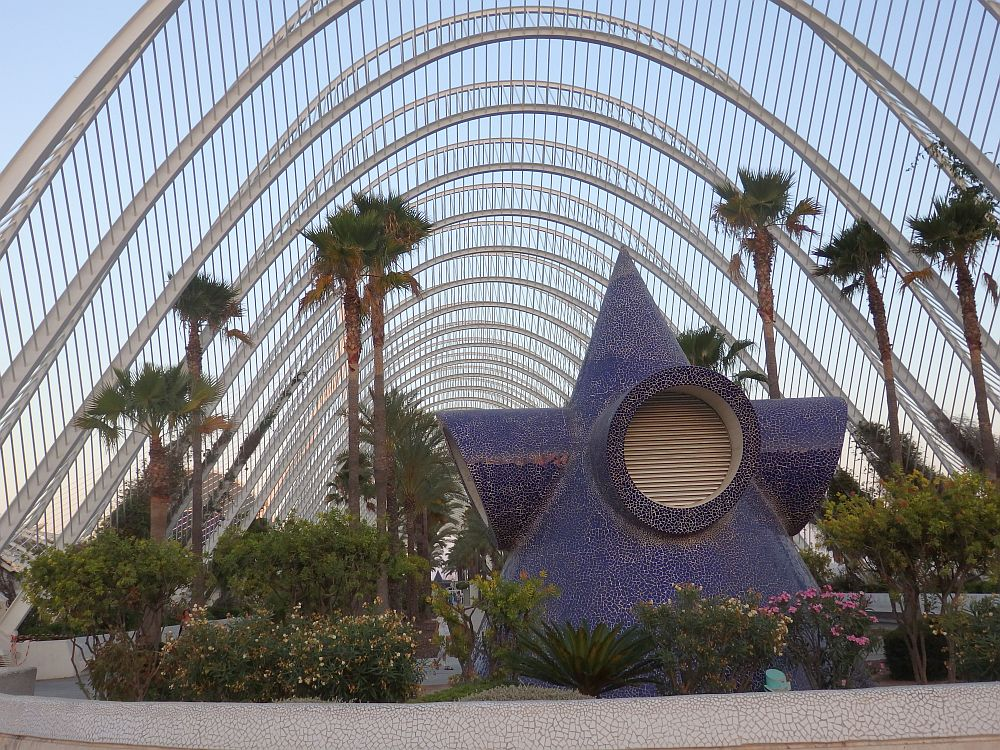 A roof that is more of a net than a roof makes a high arch above the space. IN the foreground is a blue mosaic structure that I think is a vent from the garage below. Around it are flowers and shrubs and behind it are a number of tall palm trees.