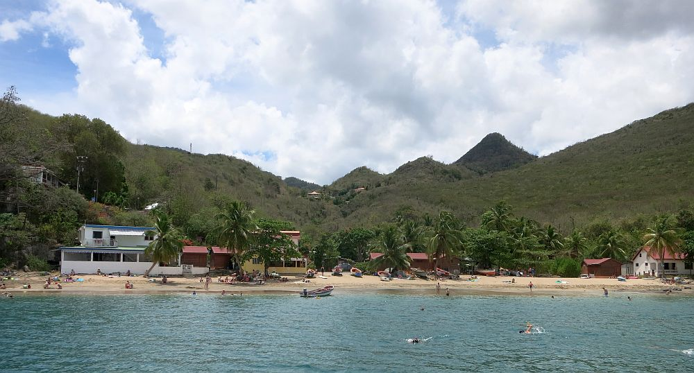 A view of a small beach as seen fro m the water, hills covered in greenery rise behind it. The beach has a lot of palm trees along it and only a few small buildings. A few people swim in the water or stand or lie on the beach.