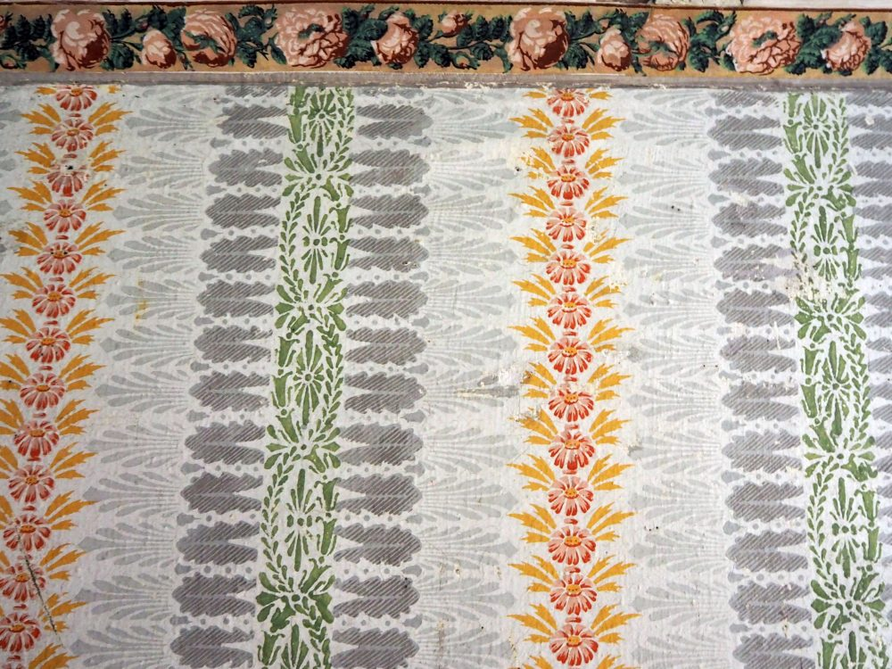 The stenciled patters repeat vertically right to the ceiling molding, which is painted in pink roses with green leaves. The patterns also repeat horizontally: left to right: a vertical line of red flowers with yellow leaves, then a light grey spray of leaves, a dark grey spray of leaves, a green pattern of flowers and leaves, then back to dark gray, light gray and then the red and yellow again.