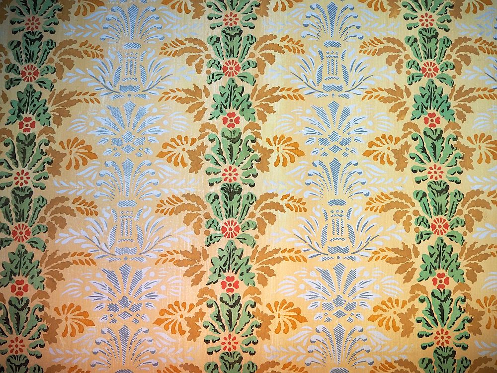 Walpaper with vertical patterns. A small red flower, green leaves above it, yellow leaves outside of that. This is repeated vertically. Between these rows are much simpler patterns in light gray and white.