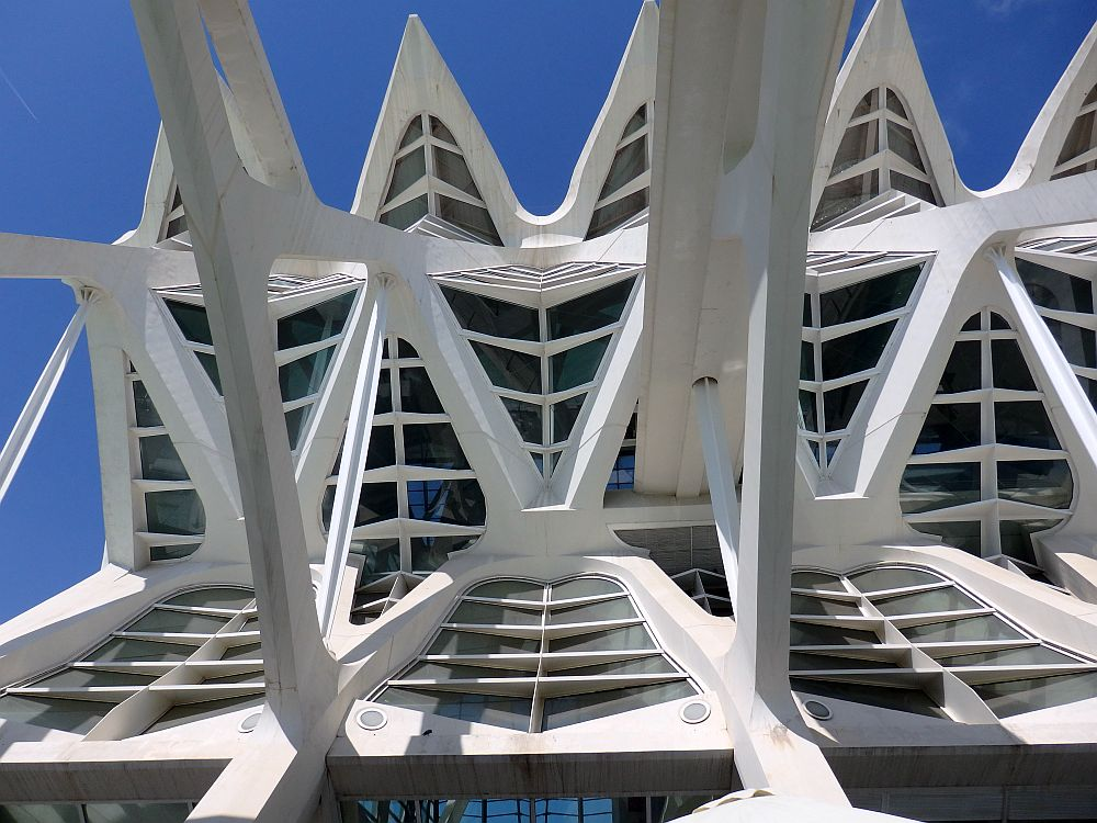 White concrete against a bright blue sky. It's a complex pattern of horizontal ribs and a shape (the roof edge) of points of triangles.