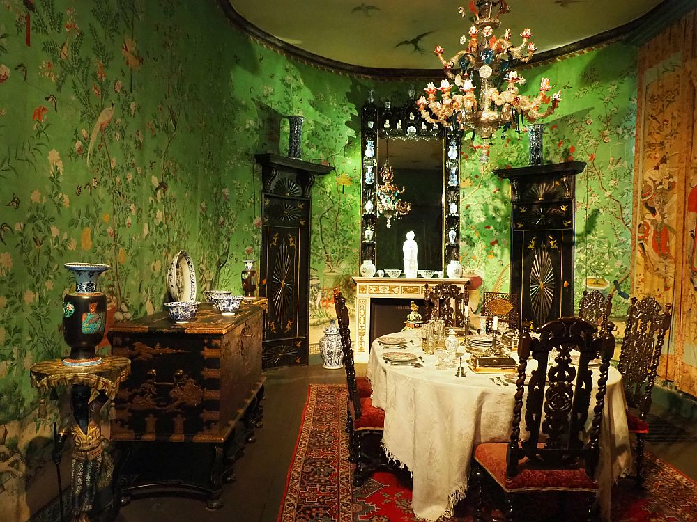 The walls are predominantly green with flowery images painted onto them. The table is elegantly set, with a white tablecloth and all the usuall table settings. The chandelier is rather chunky-with each candle in an ornate glass holder. Against the wall on the left is a large piece of furniture holding several pieces of Chinese porcelein.