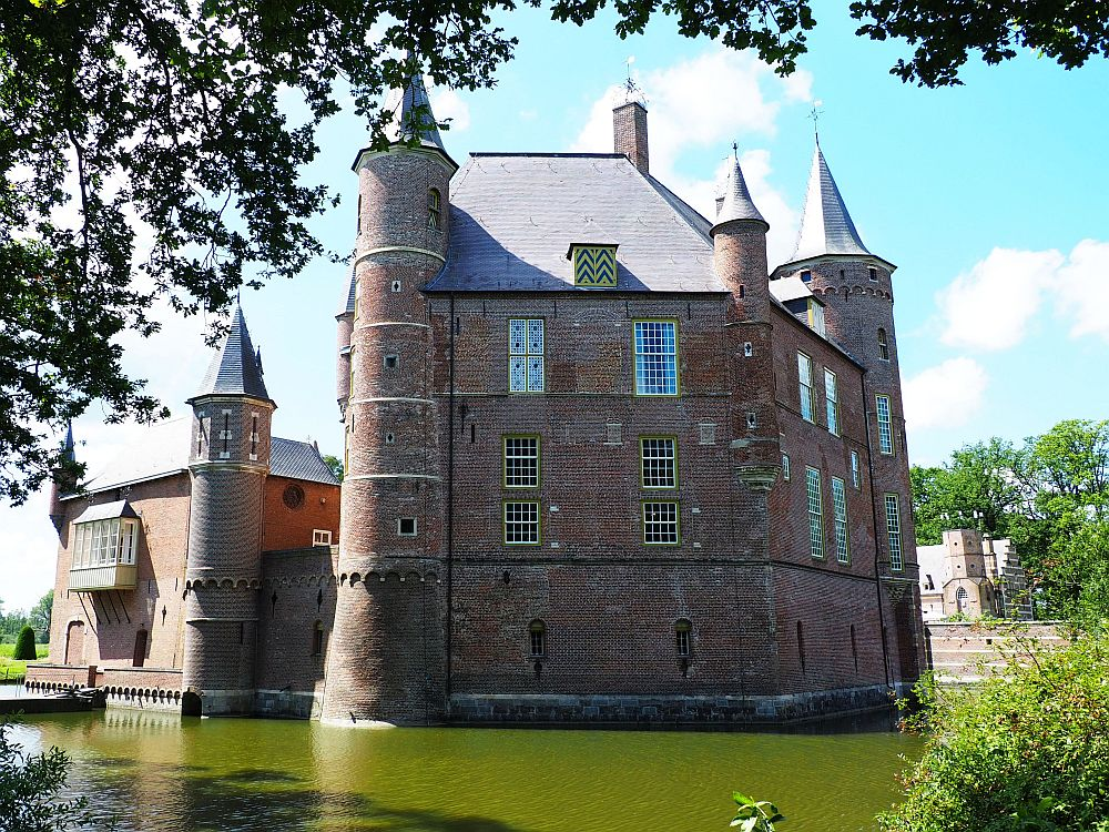 The green water of the moat in the foreground. Behind, the castle, red brick, about 4 stories high, with turrets on each corner.