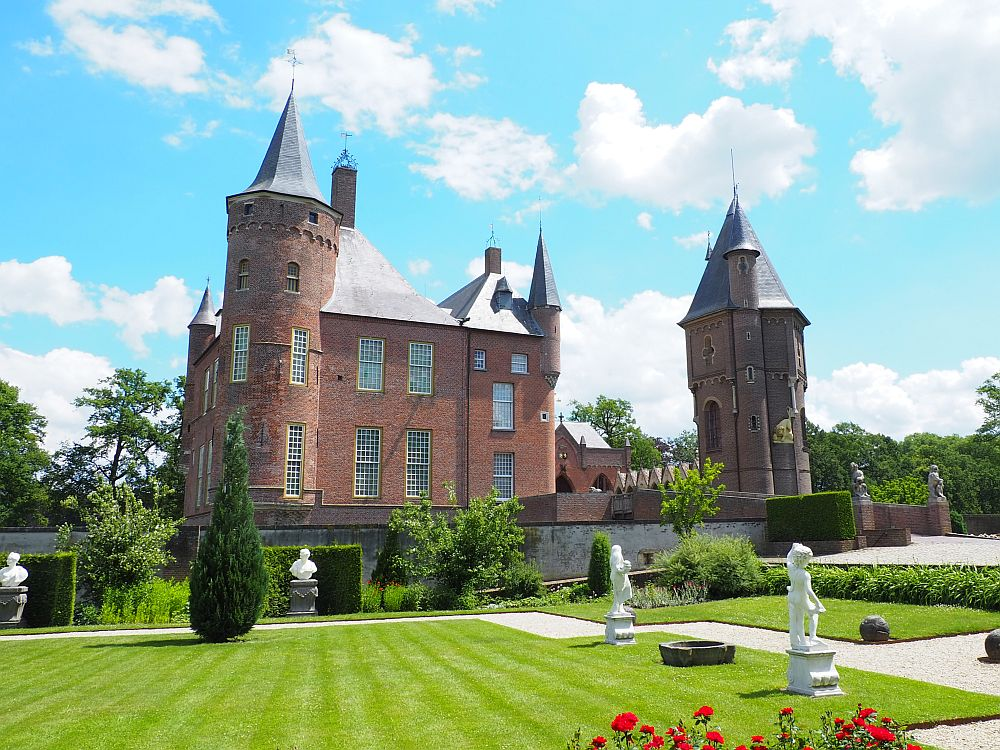 IN the foreground, very tidy green grass lawn with statues here and there. Beyond, the castle: red bricks, with a large tower in the near corner and smaller little turrets here and there, as well as a separate tower on the right.