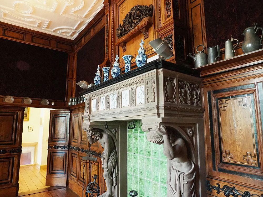 The mantel has two human figures carved into the stone, bent so it looks like they're holding up the mantel. The horizontal mantel, also stone, is ornately carved with white panels inset - maybe plasterwork? ON either side of the mantel the walls are paneled in wood, with inlays in a darker wood. The panels end about 2 meters up from the ground in a plate rail, and that is lined with a series of tankards and teapots and such in tin, except on the mantel, which has a row of blue and white porcelein vases.