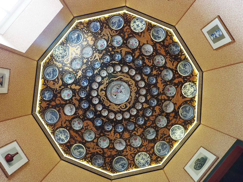 Looking straight up, a 10-sided room. The ceiling has 4 concentric circles of porcelein plates, smaller in the inner rings, getting larger to the outer ring, with a quite large one in the center. It looks like every plate is different, but the dominant colors are blue and white. Between the plates seems to be painted, mostly in a gold and black or dark blue pattern.