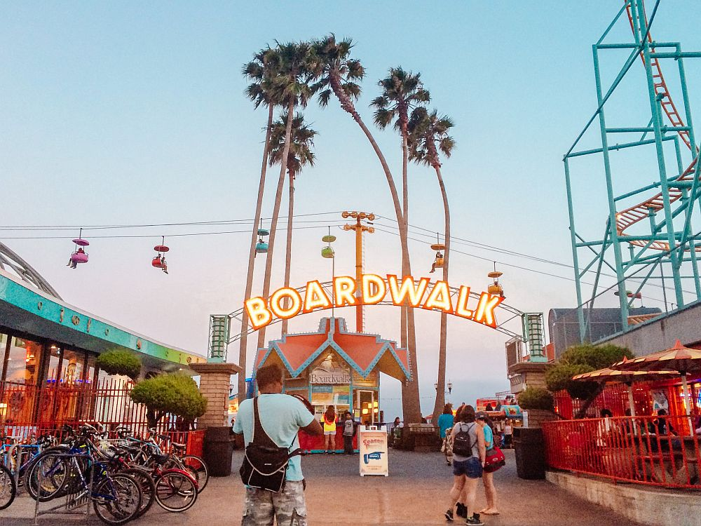 "Looking down the boardwalk: a small kiosk straight ahead with an arched neon sign above it that reads ""boardwalk"". TO the right a small part of a roller coaster track is visible. Behind the kiosk in the center is a group of about 6 very tall narrow palm trees. Beyond that is a horizontal cable where seats dangle along its length."
