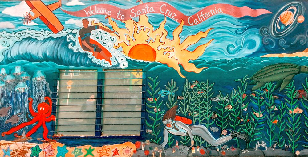 A mural saying Welcome to Santa Cruz, California. It shows a surfer, a sun set, a solar system, an airplane, and below the surfer is an underwater scene: an octopus, a group of jellyfish, a scuba diver, a turtle, some seaweed and some fish. All very colorful and cheerful.