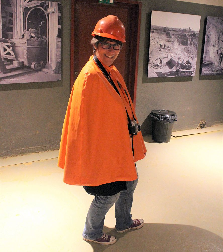 A photo of me, smiling at the camera. I wear an orange hardhat and an orange rain poncho, jeans and sneakers. A camera hangs around my neck.
