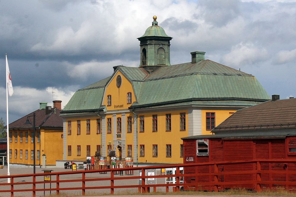 The mine building is a 3-story yellow-painted structure, symmetrical, with neat rows of windows on the ground floor and first floor. A door in the middle and 5 window on each side. The top floor is under a green roof, and only two windows near the center show, with a round window centered above them.