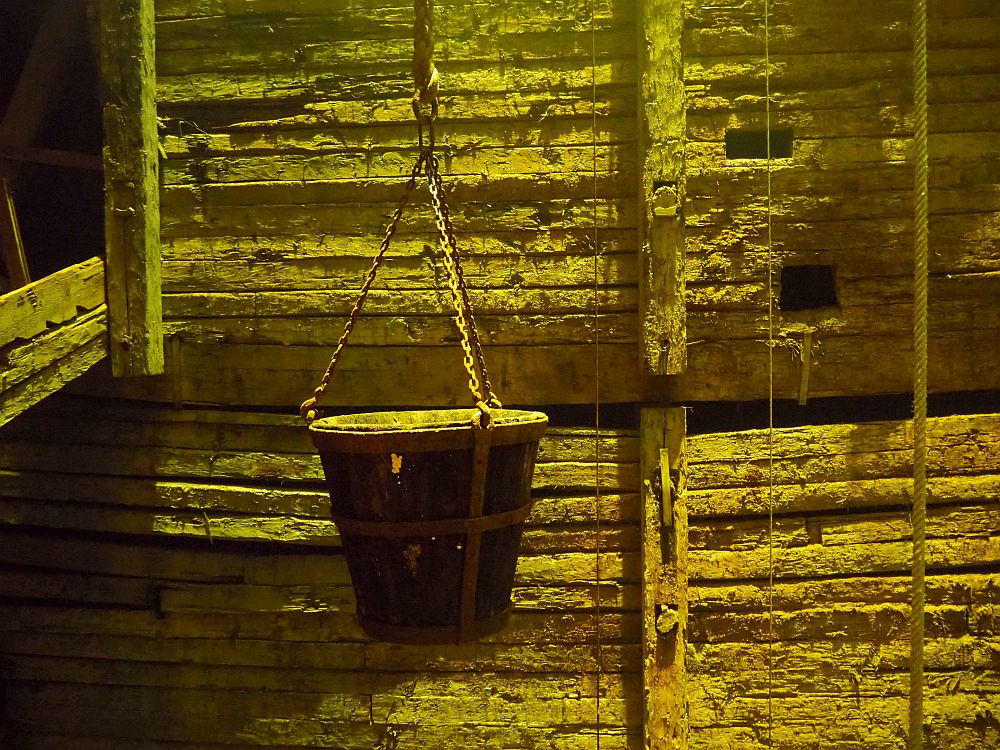 A pail hangs on a chain that connects with the pail at 3 points. Behind the pail, the wall is made of parallel horizontal strips of wood with much larger wood beams going horizontally. The whole scene has a greenish cast with indirect light from above.