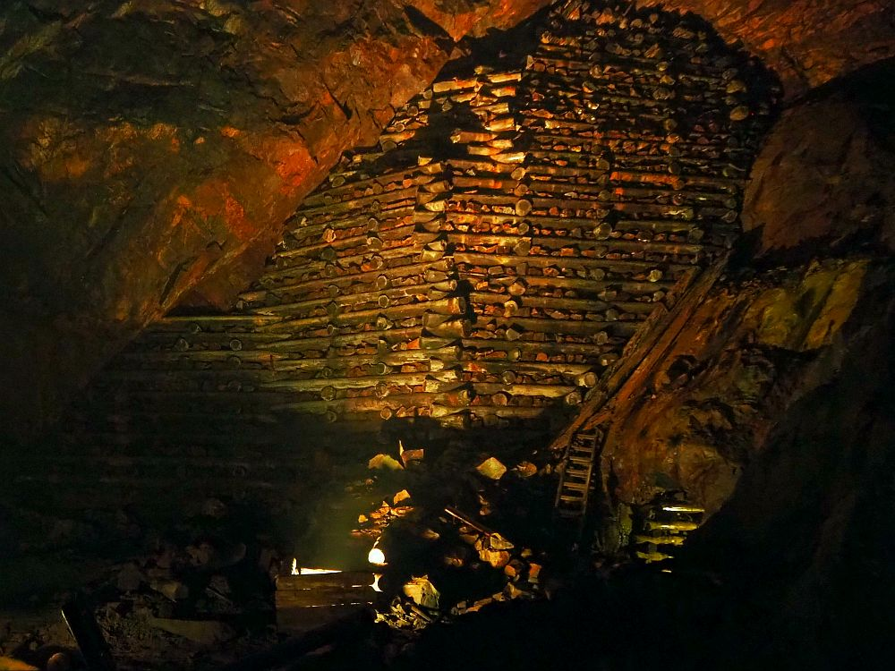 Inside a large cave, stone walls on left and right. The far wall, though, is large round logs laid horizontally, like a log cabin, but with spaces between the logs, which show rocks. All of it is a bit reddish. At the bottom is an old wooden ladder and lots of rocks.